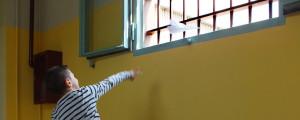 bambino che tira aeroplano di carta fuori dal carcere